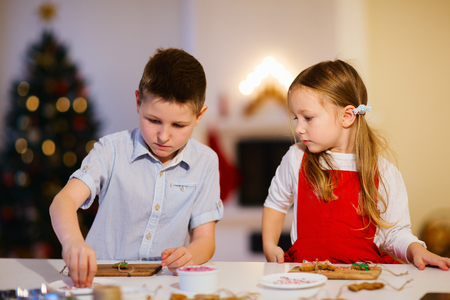 Two kids baking gingerbread cookies at home on Christmas eve photo