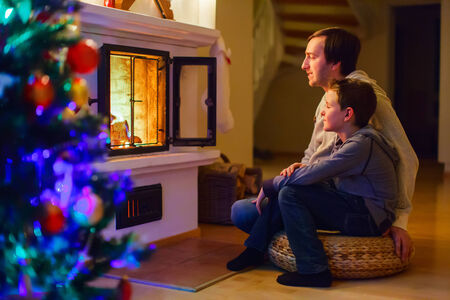 Father and his son sitting by a fireplace in their family home on Christmas eve photo