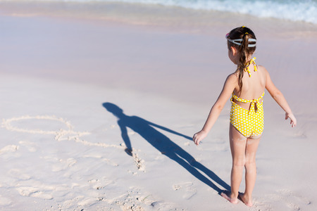 Adorable little girl having fun at beach during summer vacation photo