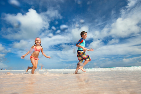 Happy Kids Running And Jumping At Beach Photo