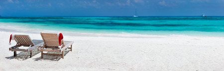 christmas scenery: Panorama of two sun loungers with Santa hats on beautiful tropical beach with white sand and turquoise water, perfect Christmas vacation