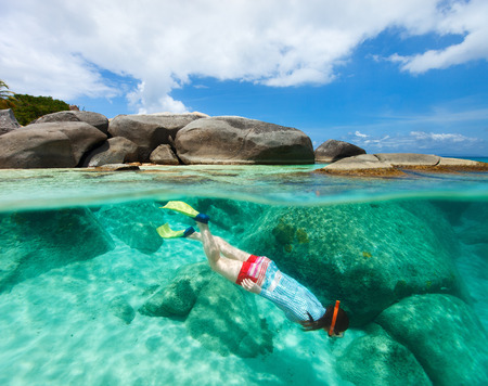 virgin: Split photo of young woman snorkeling in turquoise ocean water granite boulders on Virgin Gorda, British Virgin Islands, Caribbean Stock Photo