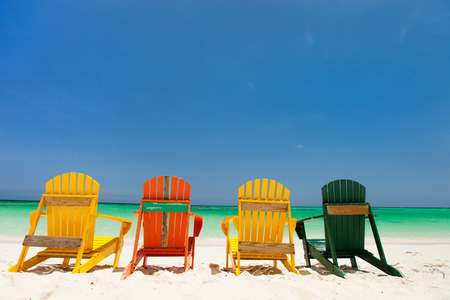 adirondack chair: Row of colorful adirondack wooden chairs at tropical white sand beach in Caribbean