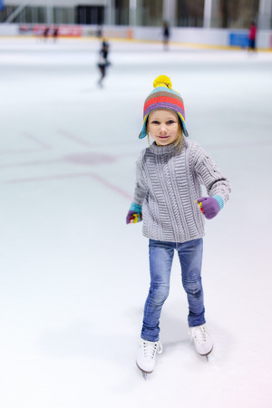 Adorable little girl wearing jeans, warm sweater and colorful hat skating on ice rink Stock Photo