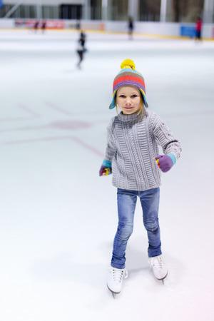 Förtjusande liten tjej som bär jeans, varm tröja och färgstarka hattskridskor på isbanan Stockfoto