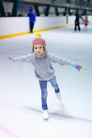 ジーンズ、暖かいセーターとアイス スケート リンクでスケートをカラフルな帽子を身に着けている愛らしい少女