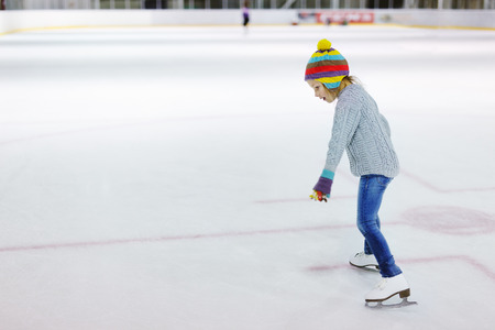 Adorable little girl wearing jeans, warm sweater and colorful hat skating on ice rink Banque d'images