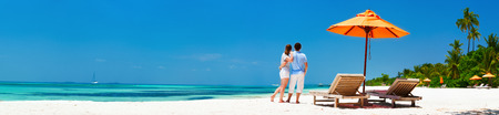 panoramic: Romantic couple on a tropical beach during honeymoon vacation, wide panorama perfect for banners