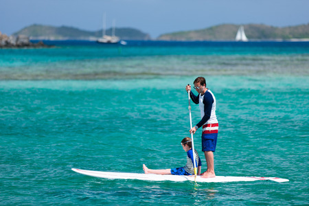paddling: Father and son paddling on stand up board having fun during summer beach vacation