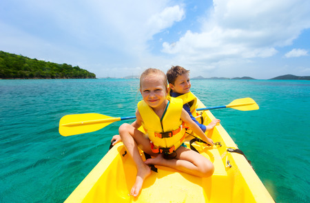 paddling: Kids enjoying paddling in colorful yellow kayak at tropical ocean water during summer vacation