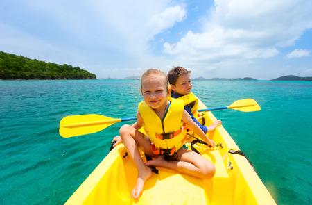 Los niños disfrutan de remar en kayak de color amarillo vivo en el agua del océano tropical durante las vacaciones de verano