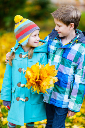 2 november: Two adorable kids outdoors in a beautiful park at sunny autumn day Stock Photo