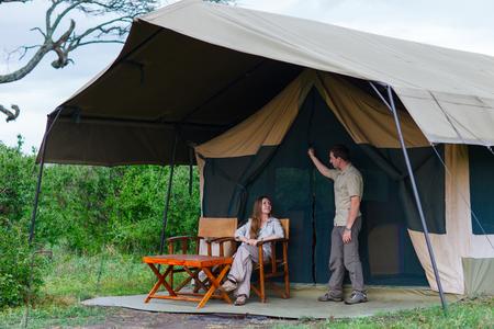 그들의 텐트 앞에 사파리 여행을 즐기는 젊은 부부 스톡 콘텐츠