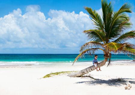 Little boy sitting on palm at Caribbean beach photo
