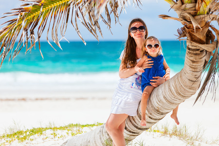 Mother and daughter sitting on palm at perfect Caribbean beach photo