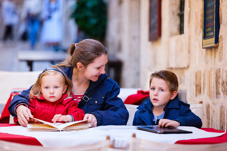 Young mother and her two kids at outdoor cafe on autumn or spring day photo