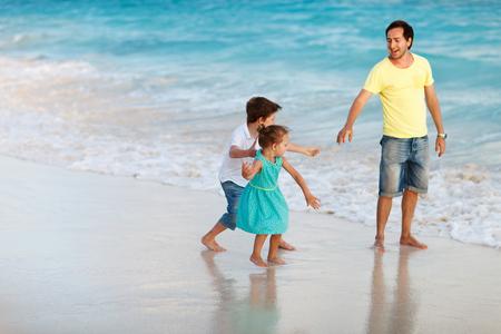 Father and kids enjoying beach vacation photo