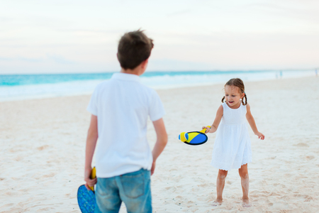 Little kids playing beach tennis on summer vacation photo