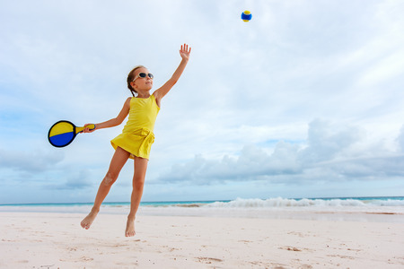 Little girl playing beach tennis on vacation photo