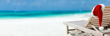 vacations: Panorama of sun lounger with Santa hat at beautiful tropical beach with white sand and turquoise water, perfect Christmas vacation Stock Photo