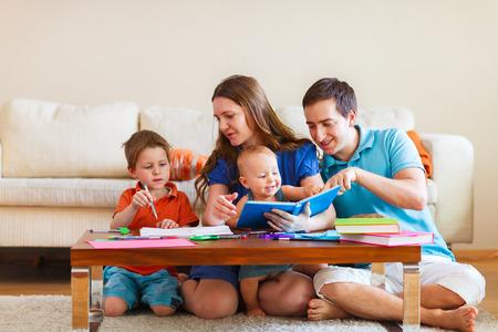 Jeune famille avec deux enfants à dessiner et à lire ensemble Banque d'images - 33198432