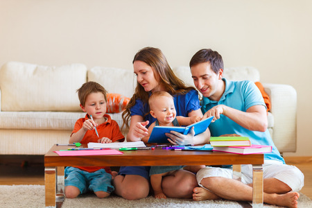 Young family with two kids drawing and reading together Stock Photo