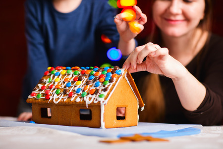 Family decorating gingerbread house on Christmas eve. Focus on house photo
