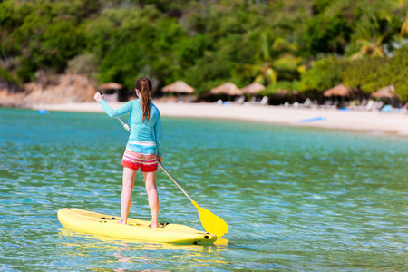 paddling: Young sporty girl on tropical beach vacation paddling on stand up board