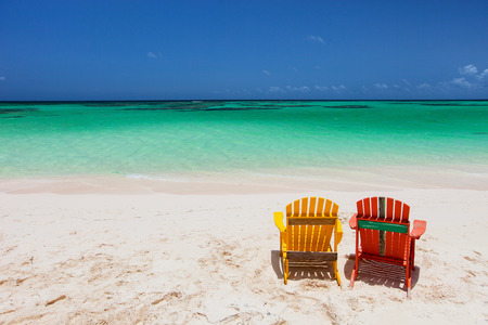 adirondack chair: Colorful adirondack yellow and orange lounge chairs at tropical beach in Caribbean with beautiful turquoise ocean water, white sand and blue sky