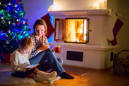 Family of mother and daughter sitting by a fireplace in their family home on winter photo