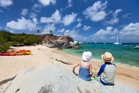Back view of two kids sitting on granite boulder and enjoying beautiful scenery of The Baths beach area major tourist attraction at Virgin Gorda, British Virgin Islands, Caribbean photo