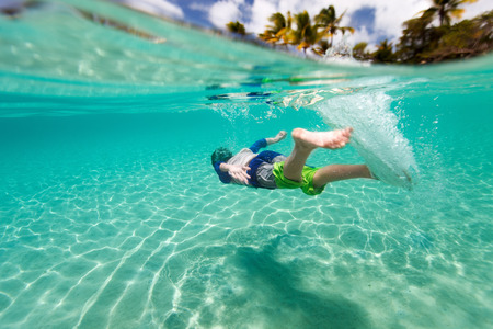 underwater diving: Cute teenage boy swimming underwater in shallow turquoise water at tropical beach