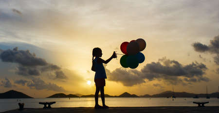 Silhouette of adorable happy little girl with bunch of balloons on sea coast at sunset photo
