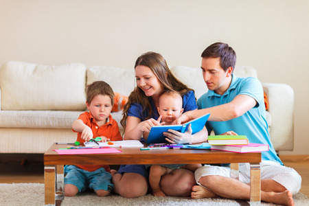 Young family with two kids drawing and reading together Banque d'images