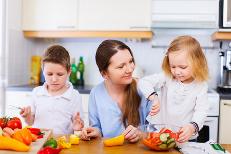 Young mother and her two kids making vegetable salad photo