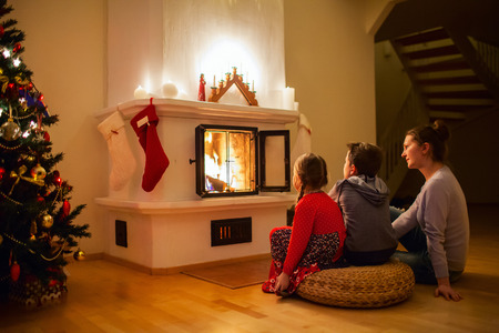 Family of mother and her two little kids sitting by a fireplace in their family home on Christmas eve photo