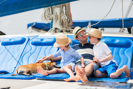 Father, kids and their pet dog sailing on a luxury yacht or catamaran boat photo