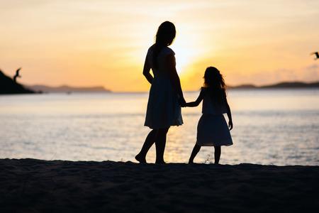 familias unidas: Siluetas de la madre y la hija caminando por la playa tropical durante la puesta de sol