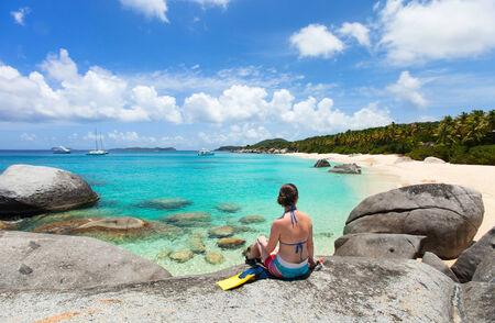 virgin: Young woman with snorkeling equipment enjoying view of a tropical beach sitting on granite boulder at Virgin Gorda, British Virgin Islands, Caribbean
