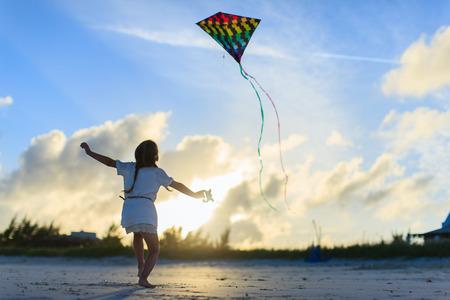 Meisje met plezier vliegeren op het strand tijdens zonsondergang