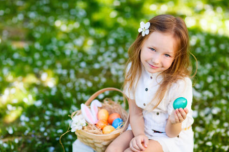 egg hunt: Adorable little girl playing with Easter eggs in a blooming garden on spring day Stock Photo