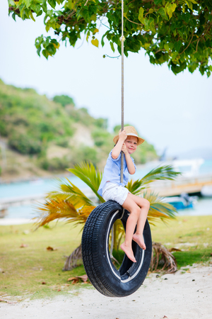 summer tire: Adorable little girl having fun on tire swing on summer day Stock Photo