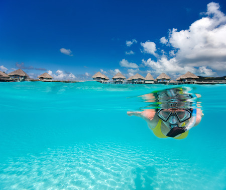 bora bora: Underwater photo of woman snorkeling in clear tropical waters in front of overwater villas