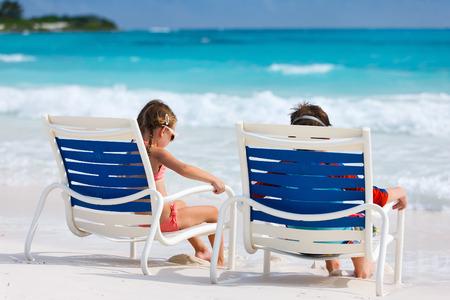 Little kids on tropical beach enjoying summer vacation photo