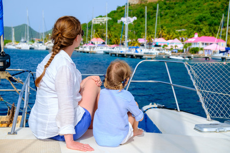 Back view of mother and daughter family sailing on a luxury yacht or catamaran boat Stock Photo