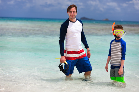 boy swim: Father and son with snorkeling equipment fins and mask at tropical beach