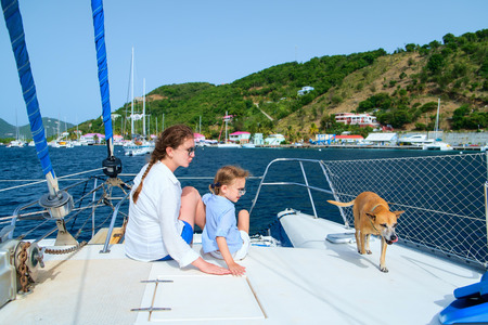 Mother, daughter and their pet dog sailing on a luxury yacht or catamaran boat photo