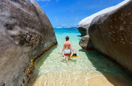 virgin girl: Young woman with snorkeling equipment at tropical beach among granite boulders at Virgin Gorda, British Virgin Islands, Caribbean Stock Photo