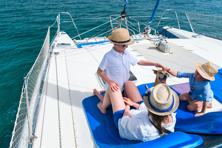 Mother and her kids relaxing having great time sailing at luxury yacht or catamaran boat Stockfoto