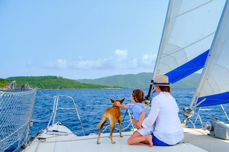 호화 요트 또는 뗏목 보트에서 항해하는 어머니, 딸 및 애완 동물 개